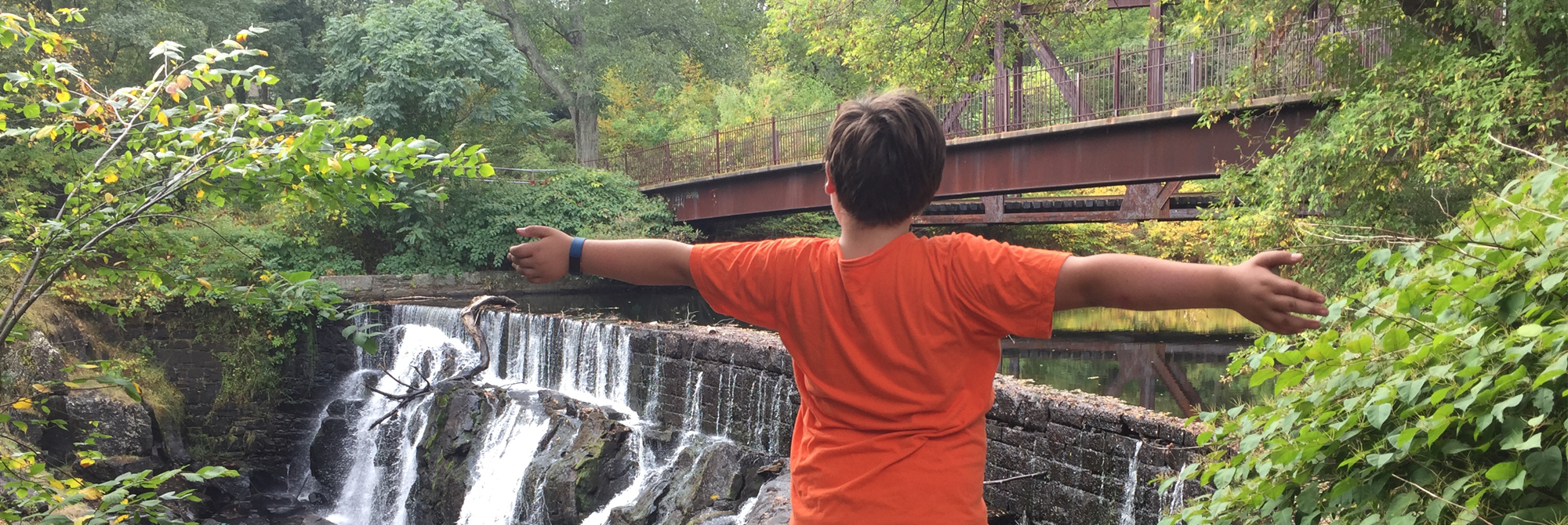 Boy with open arms at Uncas Falls in Norwich