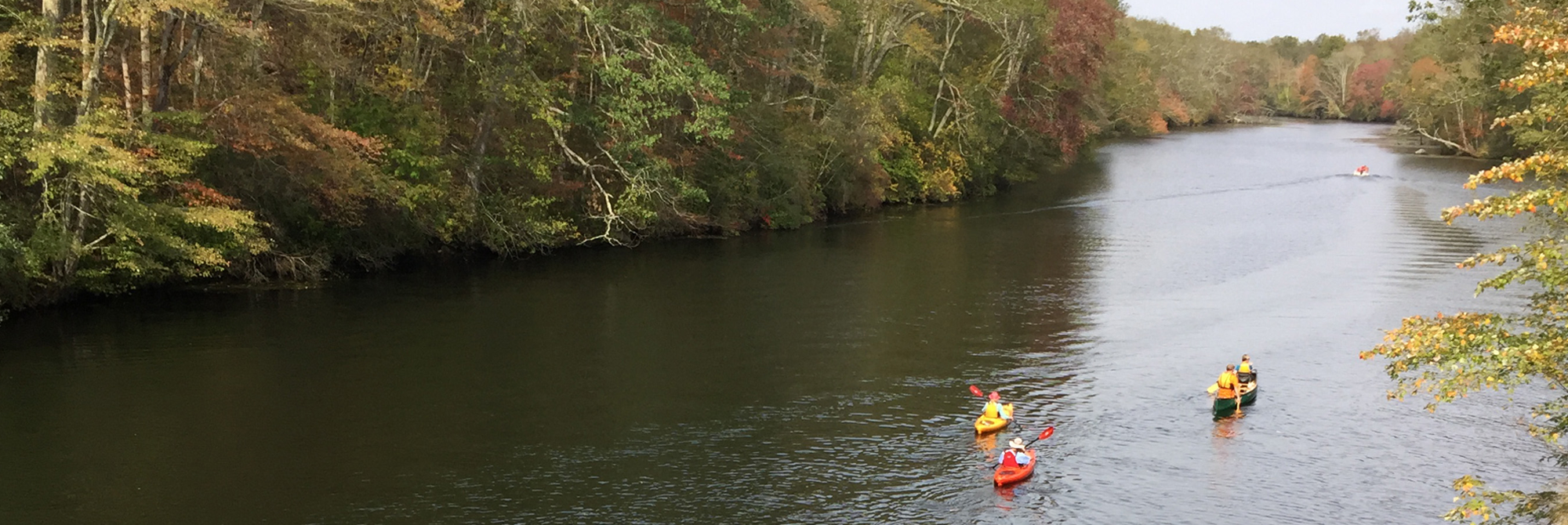 Kayaks paddling on Quinebaug River near Butts Bridge Road with leaves beginning to change color.